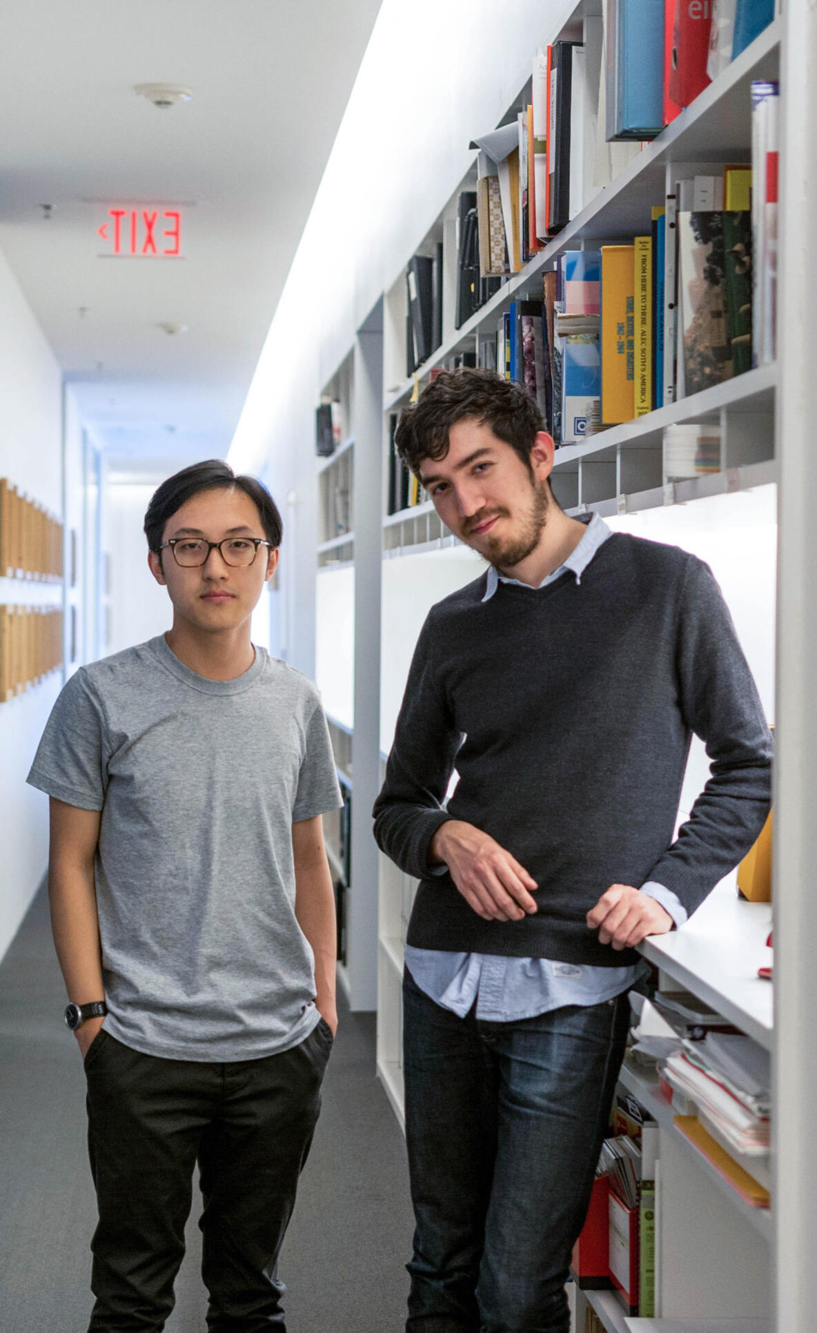 Two students standing in a room with bookshelves behind them