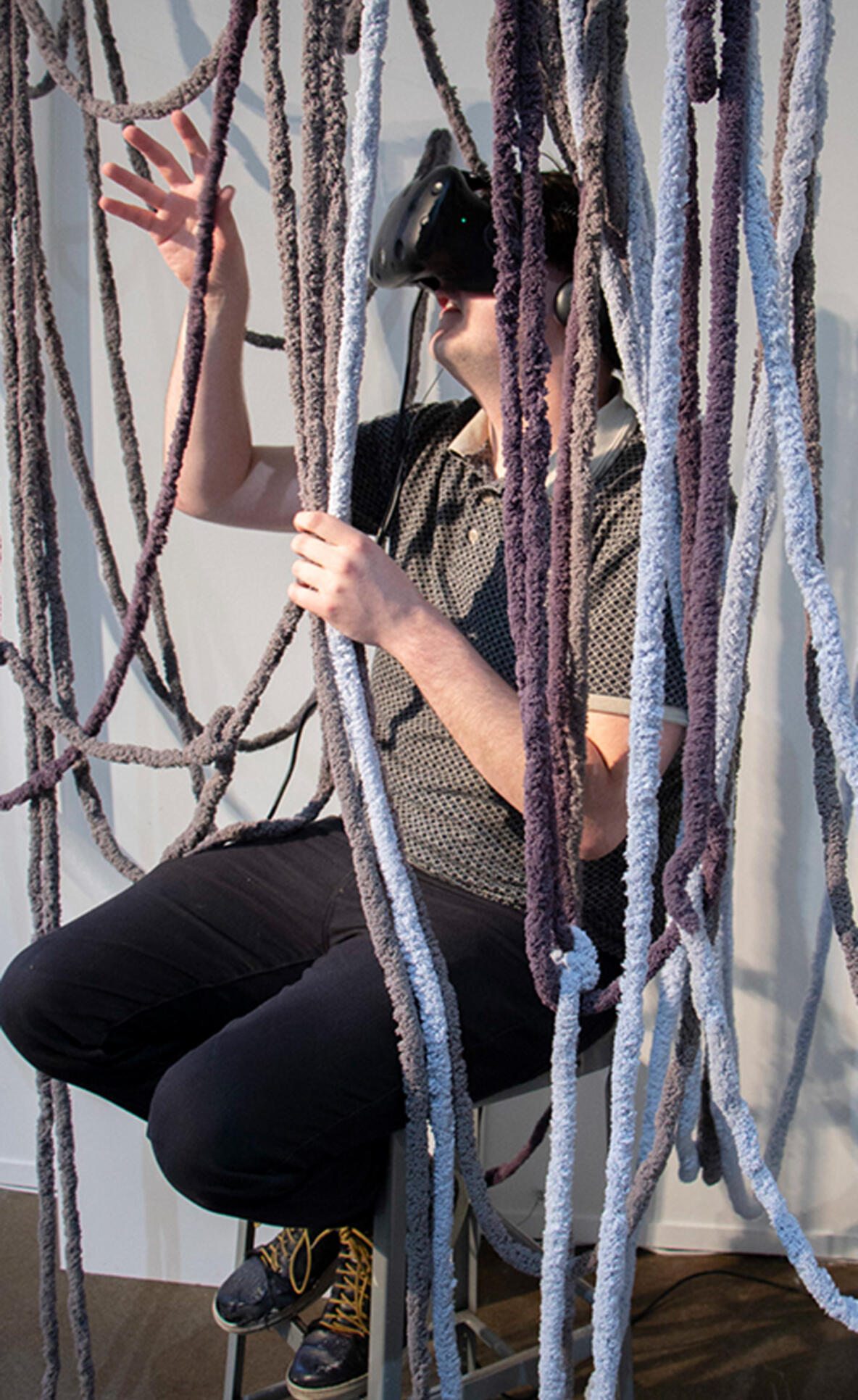 Someone is seated touching multiple ropes with a virtual reality headset on ; Shirin Ghoraishi
