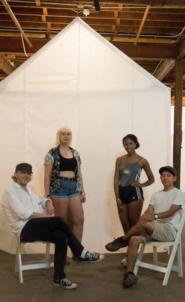 Three students and their professor pose in front of their collaborative project
