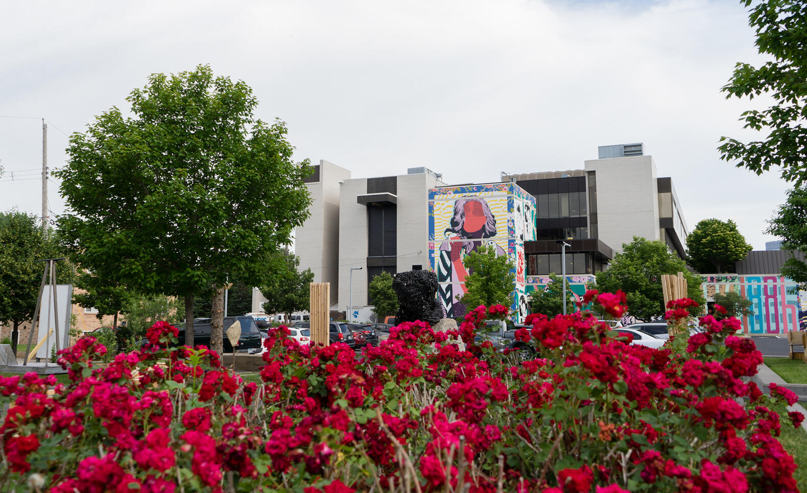 MCAD's FAILE mural, viewed behind a group of flowers.