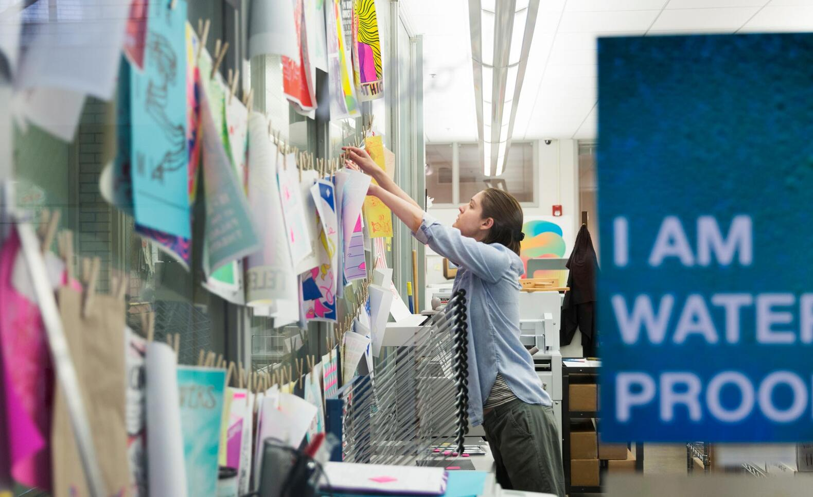Person hanging up artwork in the Service Bureau