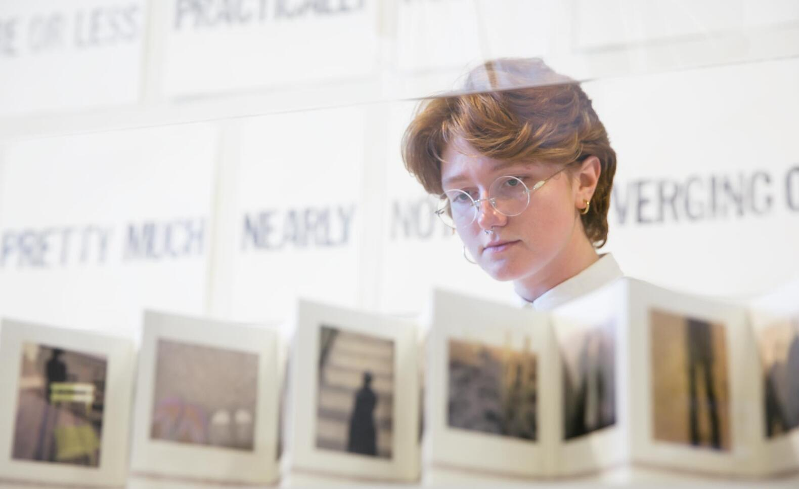 Person looking at an artist book at the MCAD Faculty Biennial