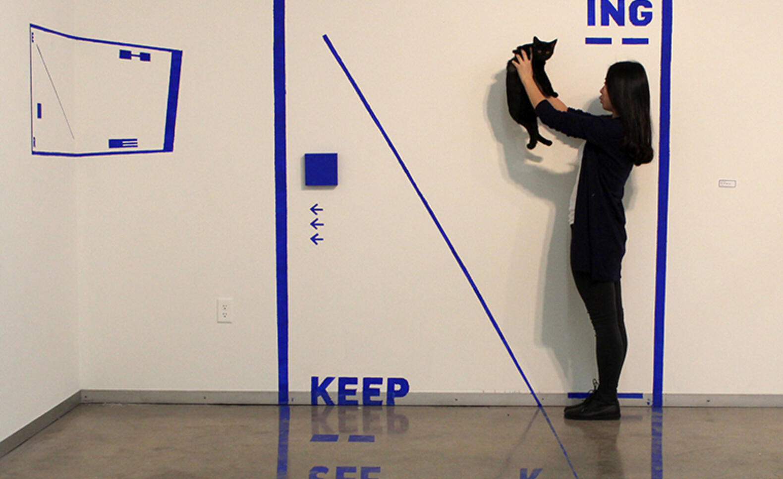 Person shown standing within a cutout of a blue rectangle holding up a cat with several words and other shapes surrounding them ; Liyuan Tong