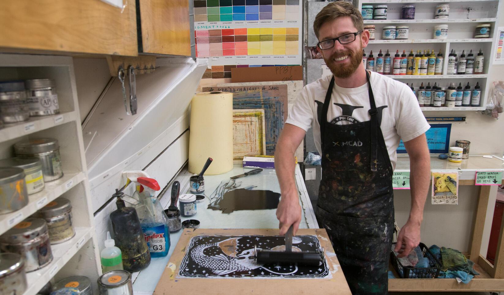 Art teacher inking a block to print