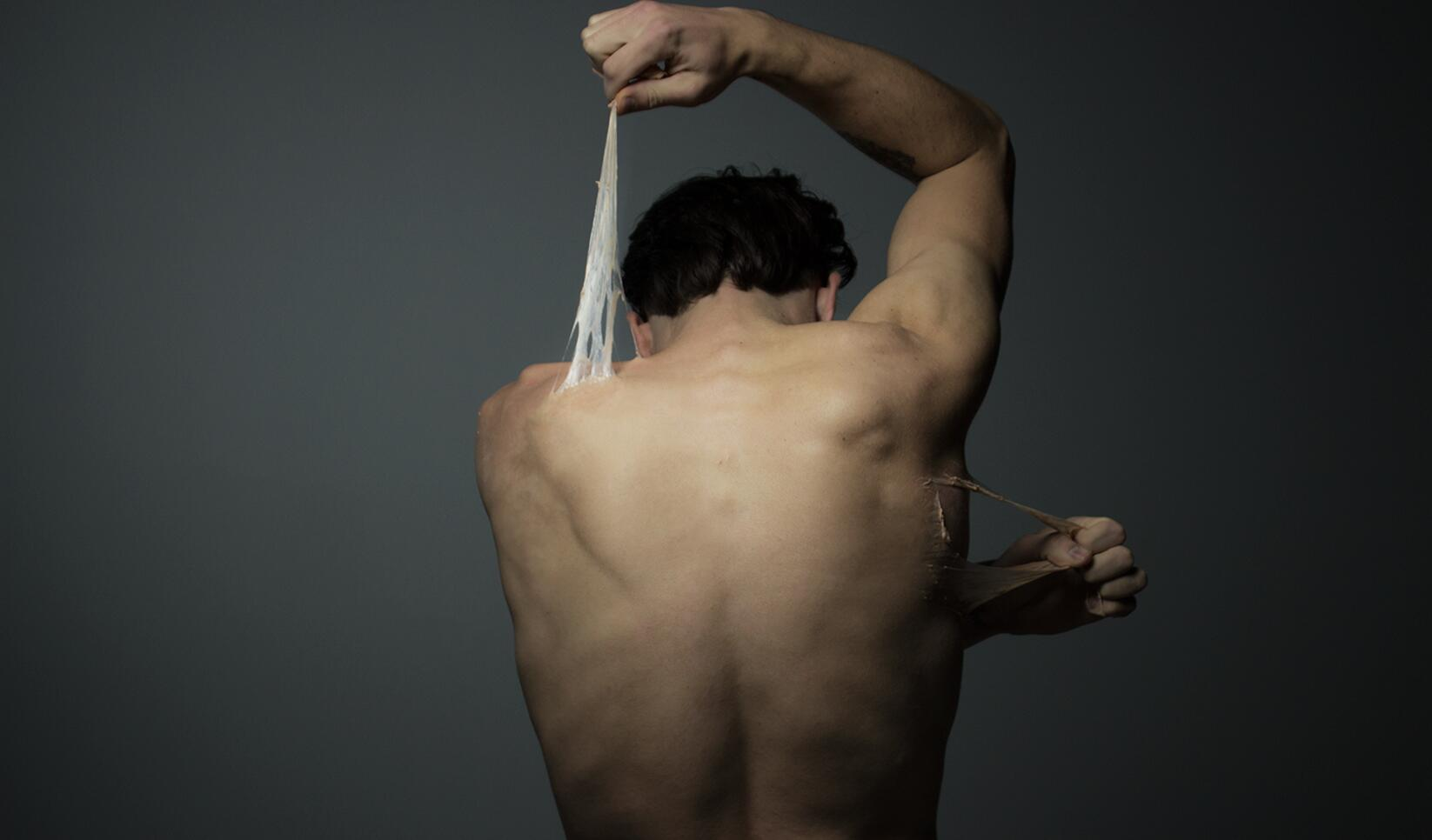 Dramatic portrait photograph of a figure pulling at their skin. ; Austin Eckstrom