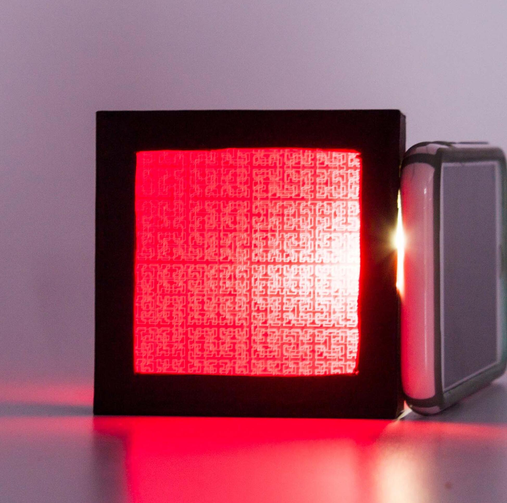 A black frame captures a red screen in which the light source behind it exposes a printed pattern. ; Alex Bacalso